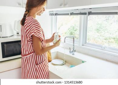 Teenage girl washing dish in the modern white kitchen. 12 years old girl doing housework.