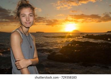 Teenage girl watching sunset on a tropical island