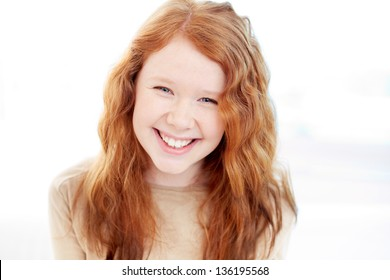 Teenage girl with wavy ginger hair looking at camera with smile