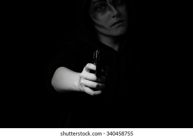 Teenage girl with weapon pointing towards camera in dark background. Selective lighting on hand and weapon. Teen violence concept.