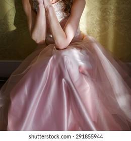 Teenage girl wearing fancy prom pink dress, posing on  school-leaving party.