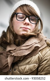 Teenage girl wearing fashionable eyeglasses with retro frames and white knit hat