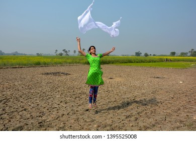 A teenage girl wearing a green salwar kameez with a white dupatta/cloth in her hands, flying it and enjoying in a harvested field with yellow mustard/rapseed flowers in the background and blue sky, se