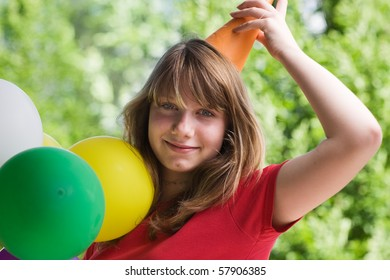 Teenage girl wearing party hat, holding balloons, Portrait