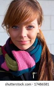 Teenage girl wearing scarf, smiling, looking at camera