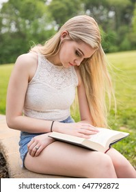 Teenage girl, wearing shorts, in the park with a book during the summer.