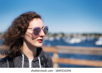 A teenage girl wearing sunglasses standing on a pier near the salem willows yacht club at willows park in Salem Massachusetts on a sunny day.