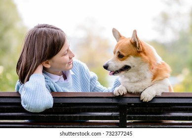 A teenage girl and a welsh corgi pembroke sitting on a bench looking at each other
