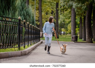 Teenage girl and a welsh corgi pembroke puppy running along the alley looking at each other