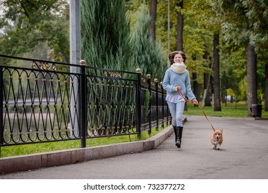 Teenage girl and a welsh corgi pembroke puppy running along the alley