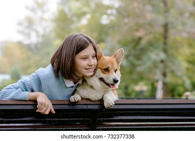 A teenage girl and a welsh corgi pembroke sitting on a bench looking to the left
