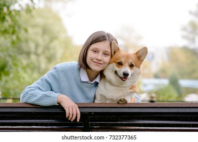 A teenage girl and a welsh corgi pembroke sitting on a bench hugging and smiling