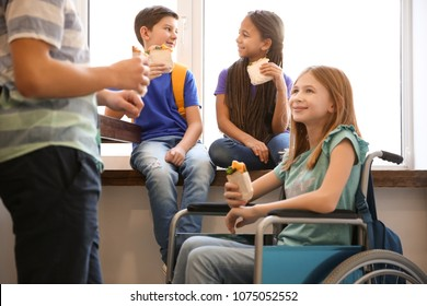 Teenage girl in wheelchair with classmates eating sandwiches at school