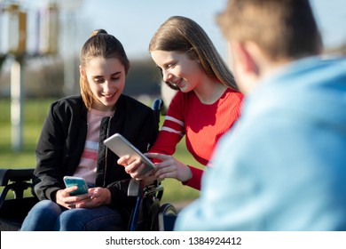 Teenage Girl In Wheelchair With Friends Looking At Social Media On Mobile Phones In Park