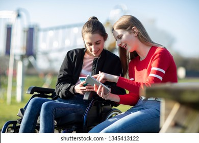 Teenage Girl In Wheelchair Looking At  Mobile Phone With Friend In Park