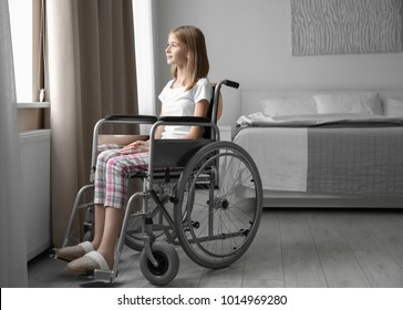 Teenage girl in wheelchair near window indoors