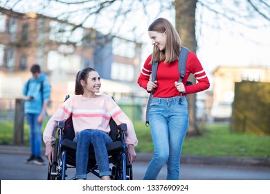 Teenage Girl In Wheelchair Talking With Friend As They Leave High School