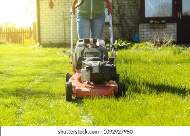 teenage girl working in garden, mowing grass with lawn-mower