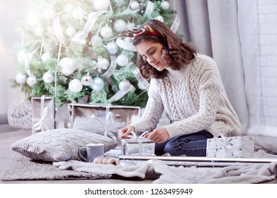 Teenage girl wrapping Christmas gifts in the morning
