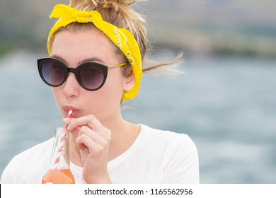 Teenage girl with yellow bandanna and sunglasses drinking from a