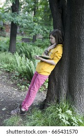 A teenage girl in a yellow hoodie reading a book leaning against a tree
