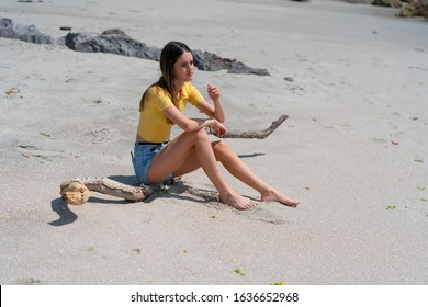 Teenage girl in yellow top and denim shorts sitting on piece of driftwood on beach at Mount Maunganui, New Zealand.