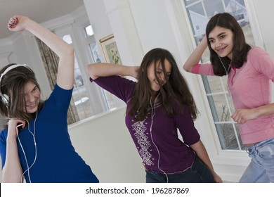 Teenage girlfriends dancing for joy to the music from headphones