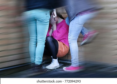 Teenage girls bullying and kicking a girl sitting down covering her face, crying. Blurred.