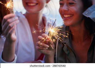 Teenage girls celebrate and smile with sparklers close up shot