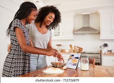 Teenage Girls Following Recipe On Digital Tablet