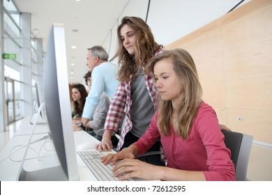 Teenage girls in front of desktop computer at school