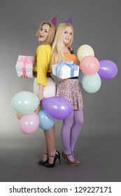 teenage girls with gifts and balloons at a birthday party over grey