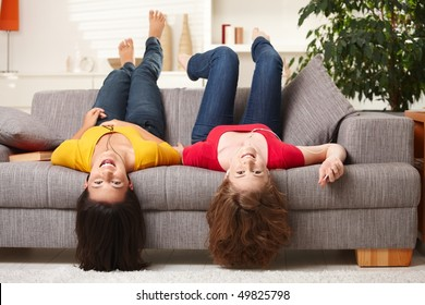 Teenage girls lying on couch upside down, looking at camera, smiling.
