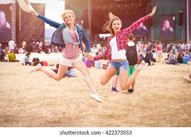 Teenage girls, music festival, jumping, in front of stage