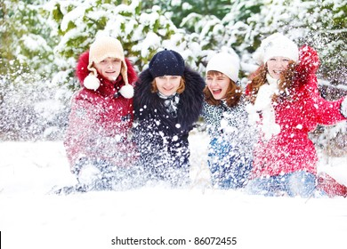 Teenage girls playing with snow in park