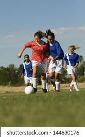 Teenage girls playing soccer on field against the sky