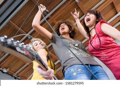 Teenage girls singing and playing guitar in band in garage