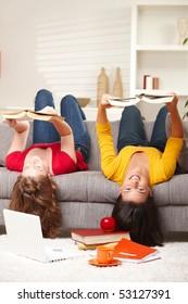 Teenage girls sitting upside down on sofa smiling holding books.