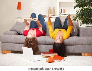 Teenage girls sitting upside down on sofa reading books.?