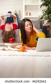 Teenage girls studying at home in living room lying on sofa and floor with books and laptop.