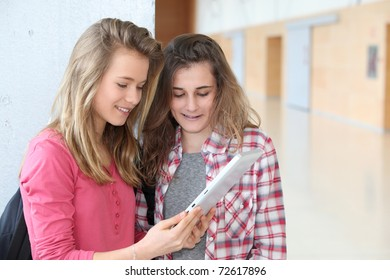 Teenage girls using electronic tablet at school
