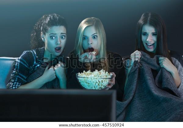 Teenagermädchen sehen Horrorfilm mit Popcorn
