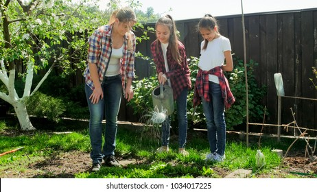 Teenage girls watering garden with young mother