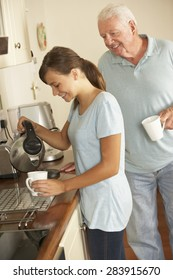 Teenage Granddaughter Sharing Cup Of Tea With Grandfather In Kitchen