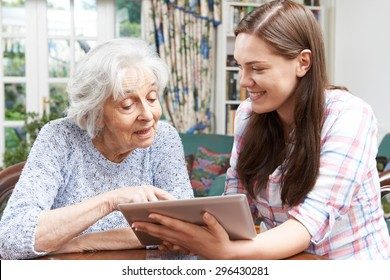 Teenage Granddaughter Showing Grandmother How To Use Digital Tablet