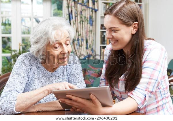 十几岁的孙女展示奶奶如何使用数字平板电脑