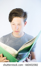 Teenage with a green binder reading from it.