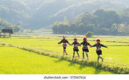 A teenage group of hilltribe in the north of Thailand enjoying in rice field, Unidentified hill tribe was running  with traditional clothes and silver jewelery in Chiang Rai