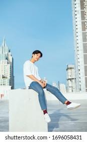 Jugendliche in Jeans und weißes T-Shirt sitzen auf der Betonkiste auf dem Dach des hohen Gebäudes in der Stadt.