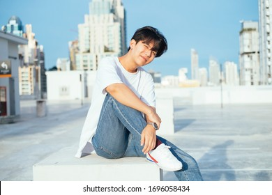 Teenage guy in jeans and white t-shirt sitting on the concrete box at the rooftoop of high building in the city in sunlight.